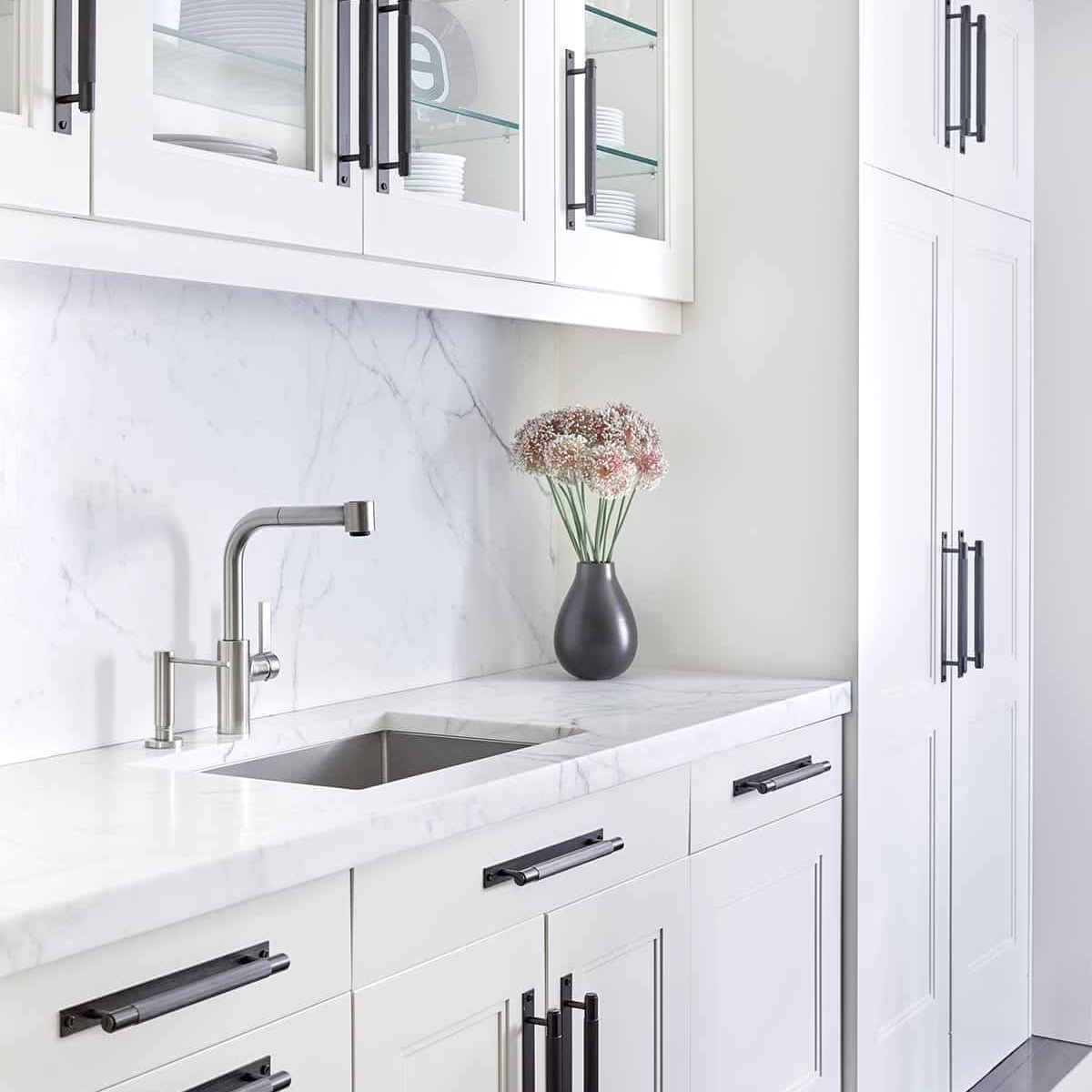 modern white kitchen with marble counter tops and marble slab backsplash and oversized black hardware