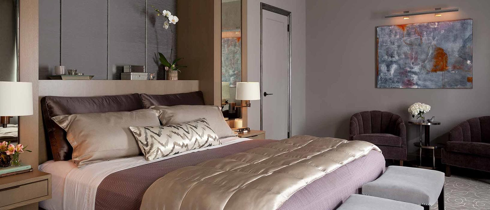 Bedroom with upholstered raw silk panels, custom millwork, asymmetrical nightstands and gray wall