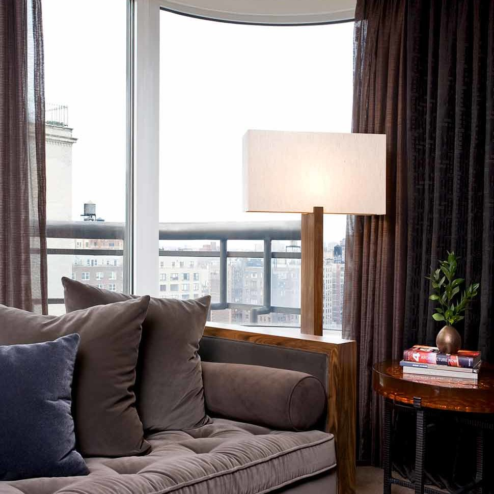 Masculine home office with a muted gray mohair sofa with button tufting in a NYC penthouse apartment