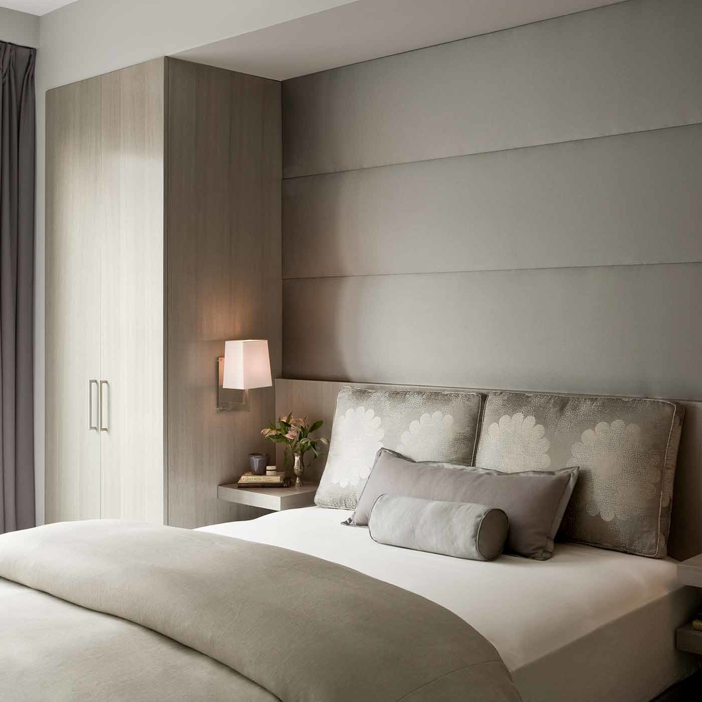 Guest bedroom design with a palette of icy lavender and champagne tones adorned with delicate sconces