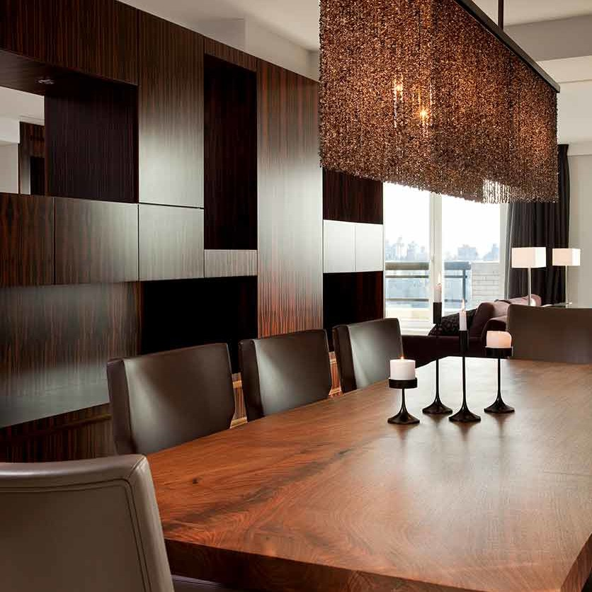 Dining room with wood and bronze table set below a stunning topaz layered chandelier in a NYC duplex apartment