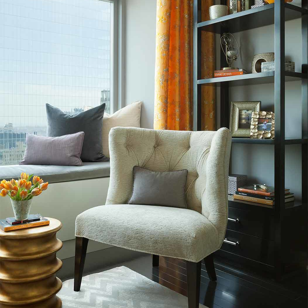 An armchair, a modern gold accent stool and an elegant black book case with transitional accessories