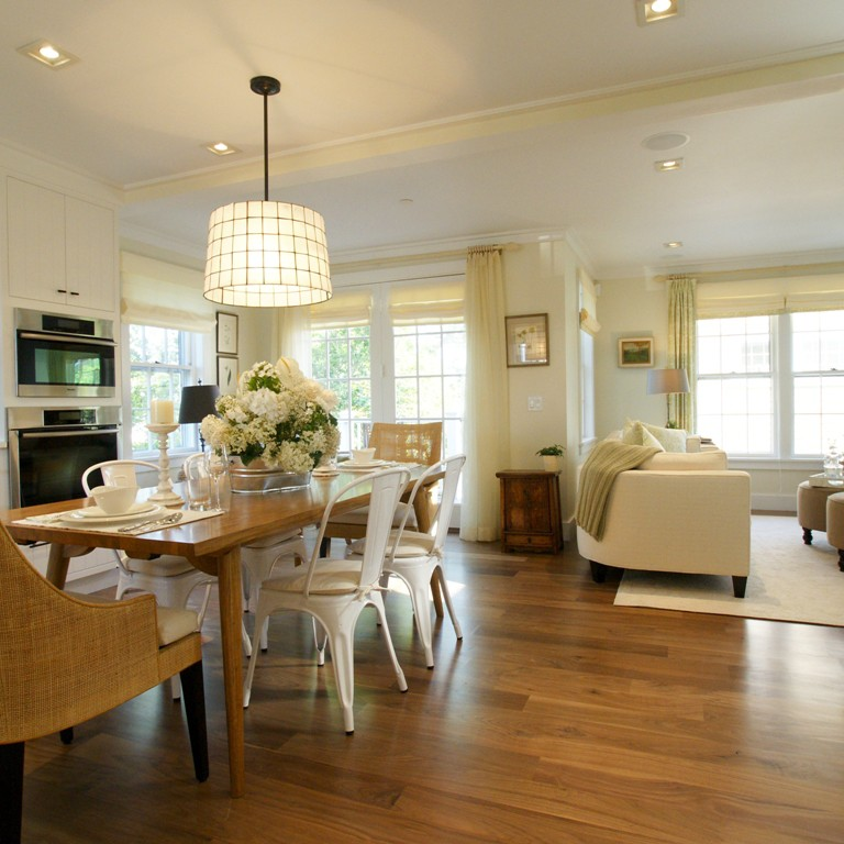 Open-concept, transitional style dining room with a happy yellow palette and medium tone wood floor