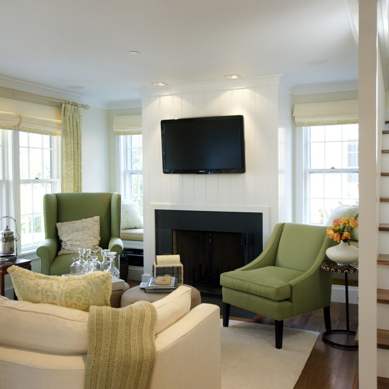 Open concept living room in Nantucket with white walls, fireplace and a wall-mounted tv designed by Darci Hether
