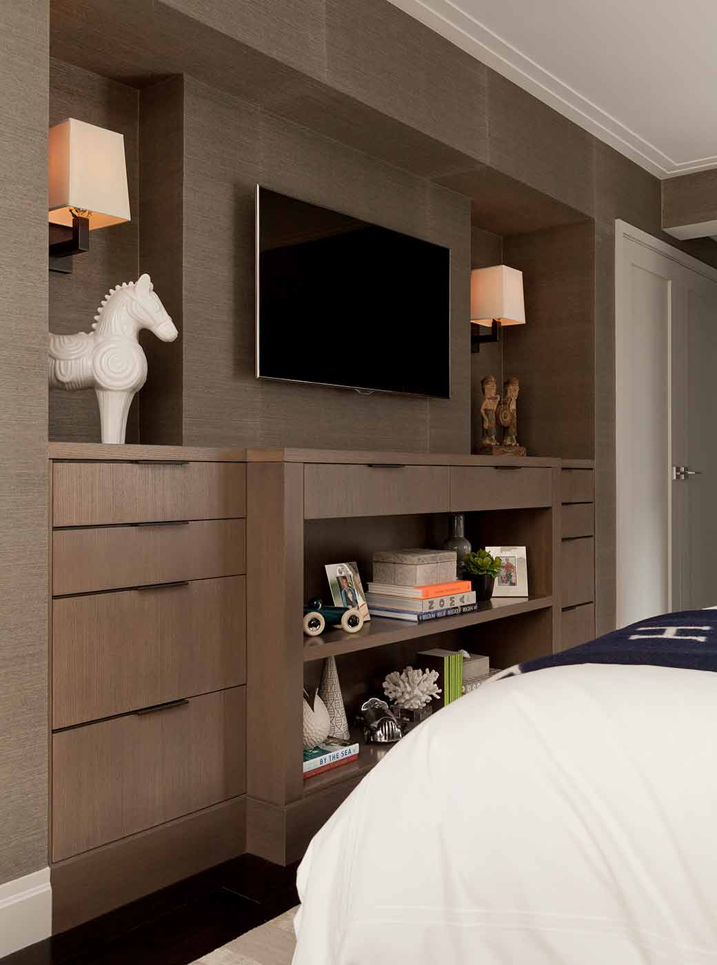 Master suite with a custom built-in for storage complete with custom hardware in the form of asymmetrical bronze bands
