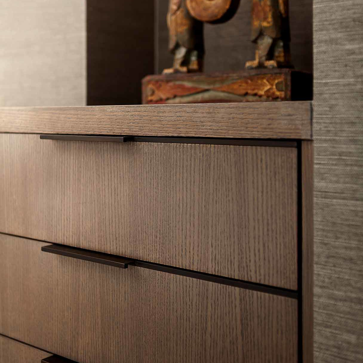 Custom built-in for storage with custom hardware in the form of asymmetrical bronze bands in a NYC apartment