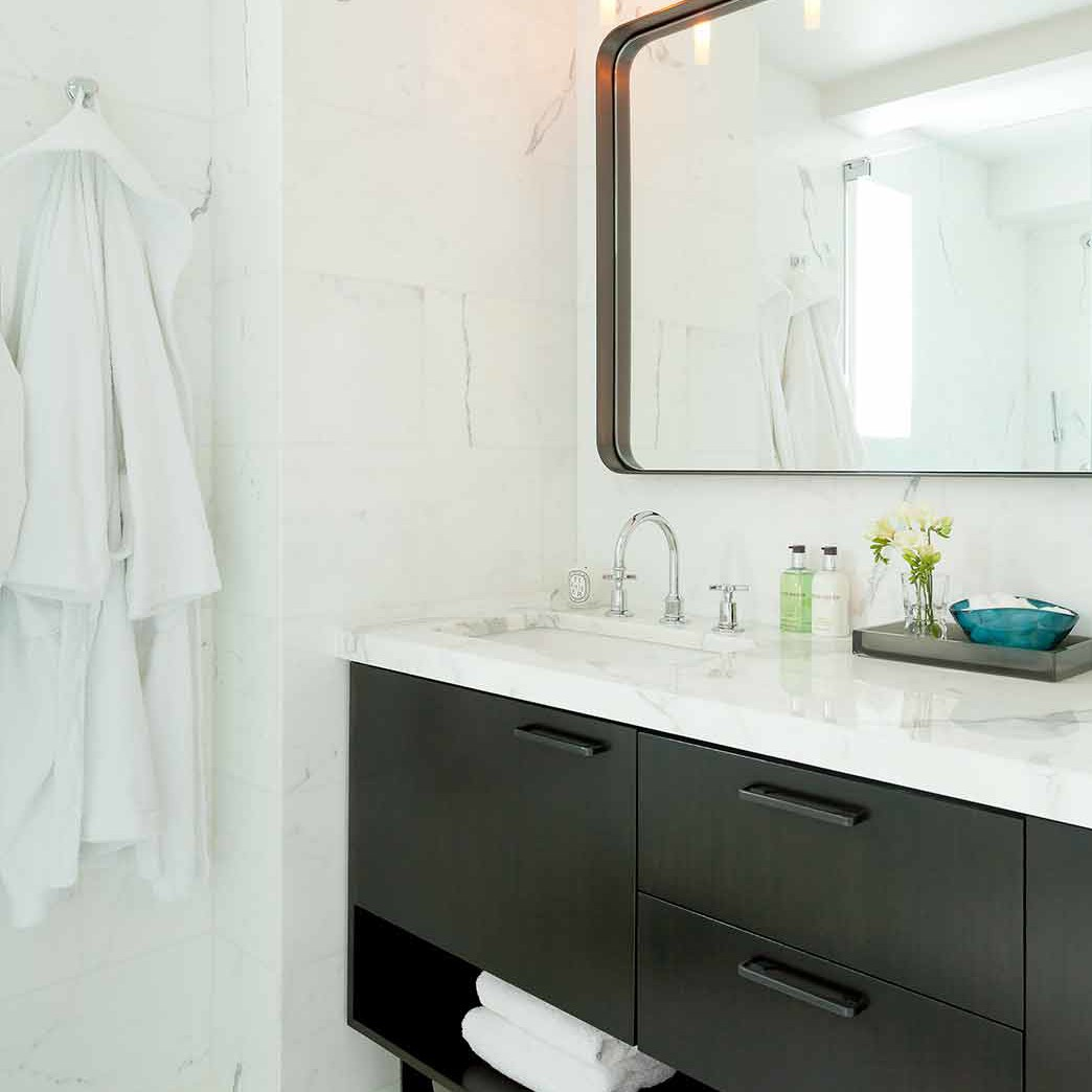 White marble master bathroom with sleek custom made double vanity and metal mirror designed by Darci Hether New York