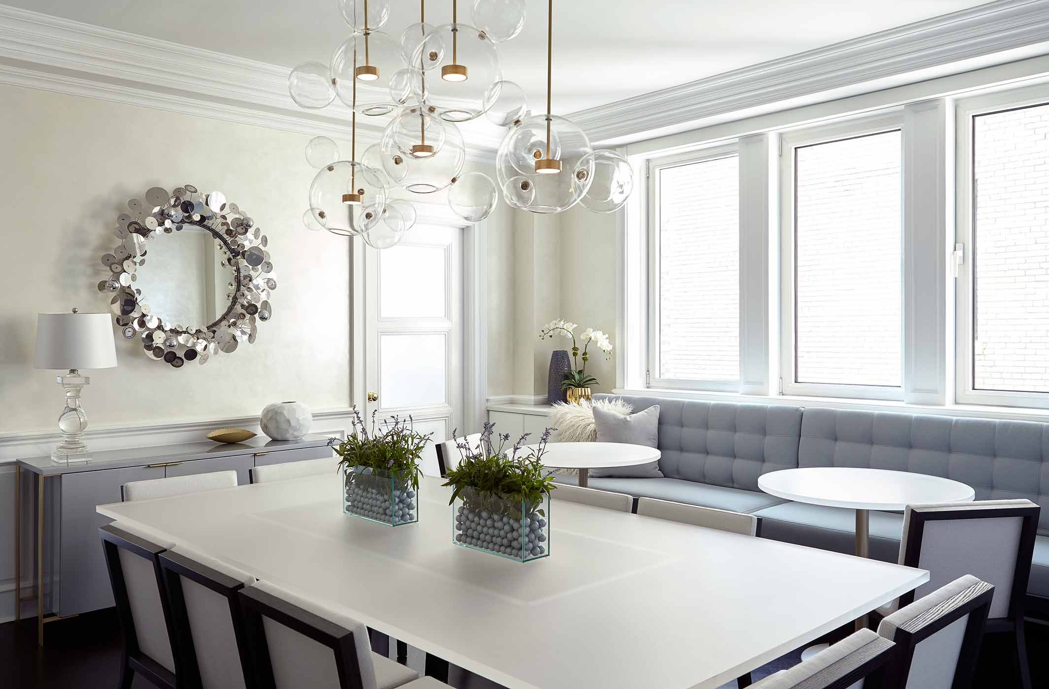 NYC dining area with custom made multi-bubble chandelier, banquette seating and bistro tables