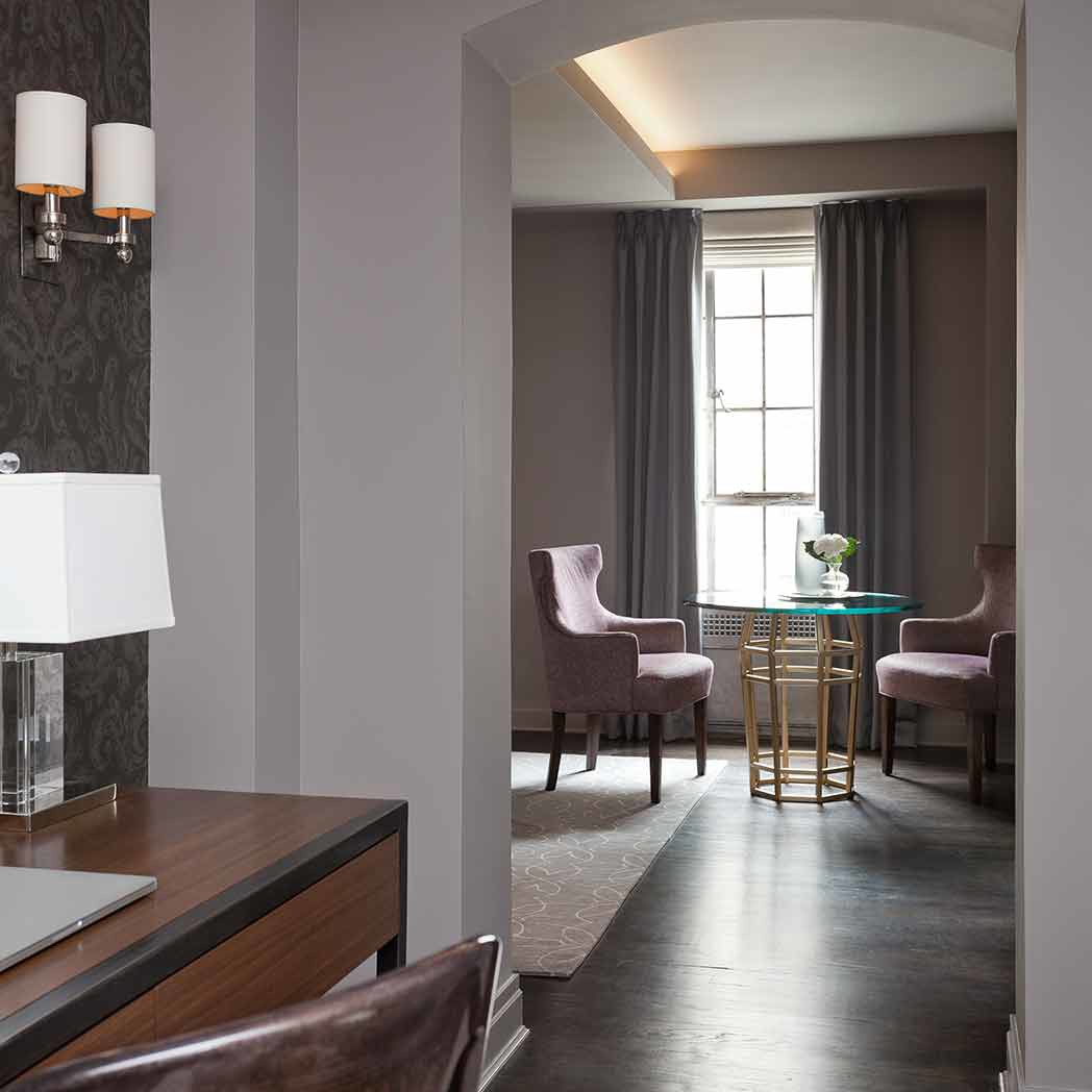 Dining area beyond the entryway with two fluted-back chairs and a custom-made table in a NYC apartment