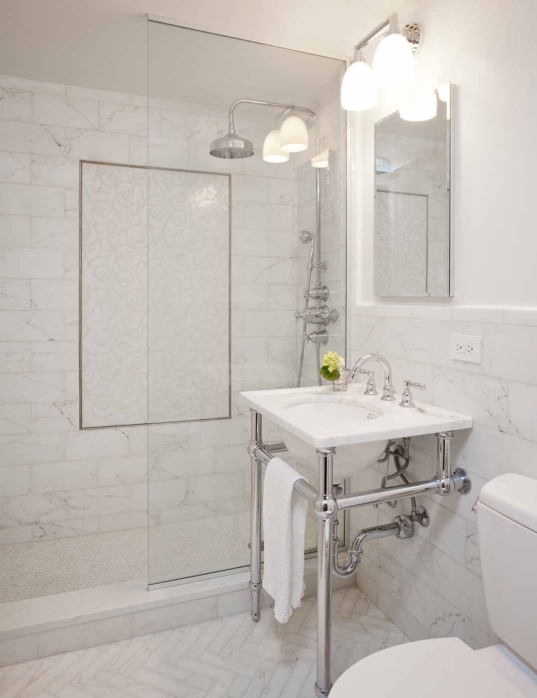 Walk-in shower with a marble field tile, floral pattern for the inset and an open pedestal sink