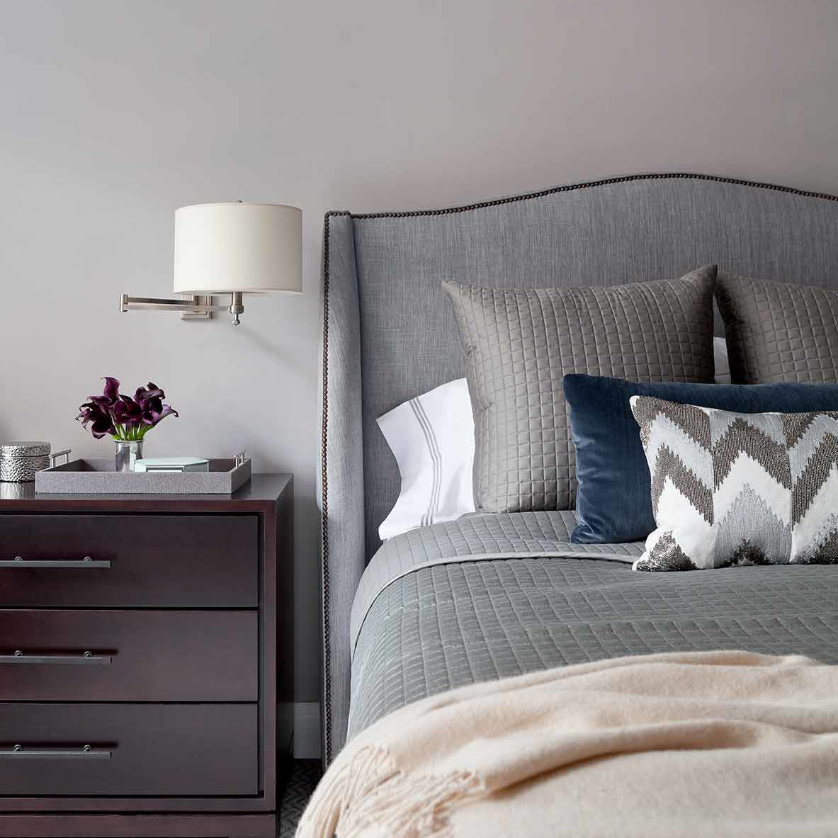 NYC apartment bedroom interior design with upholstered headboard, wall mounted sconces and storage drawers