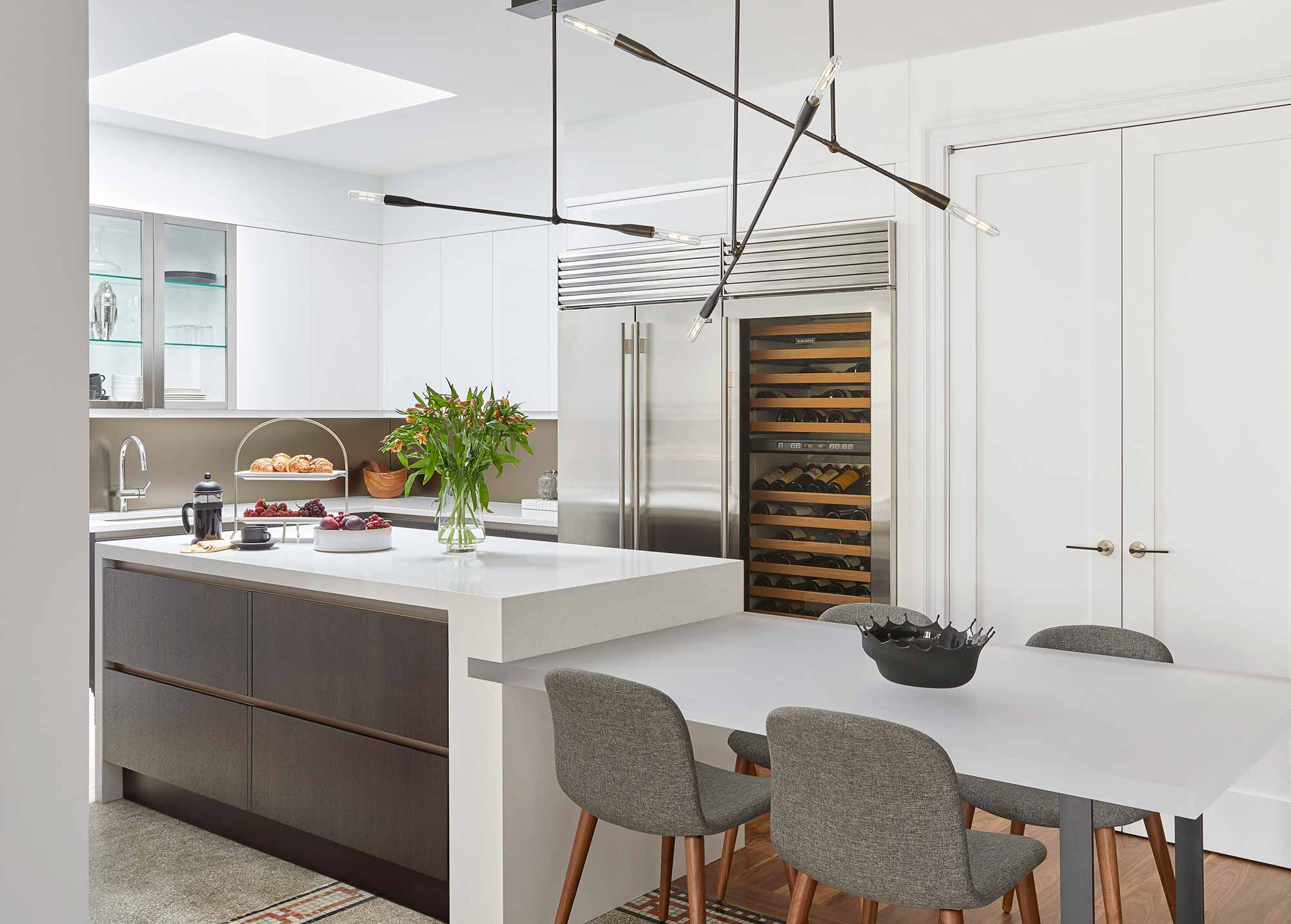 White kitchen with stainless steel appliances and swing arm pendant light designed by Darci Hether