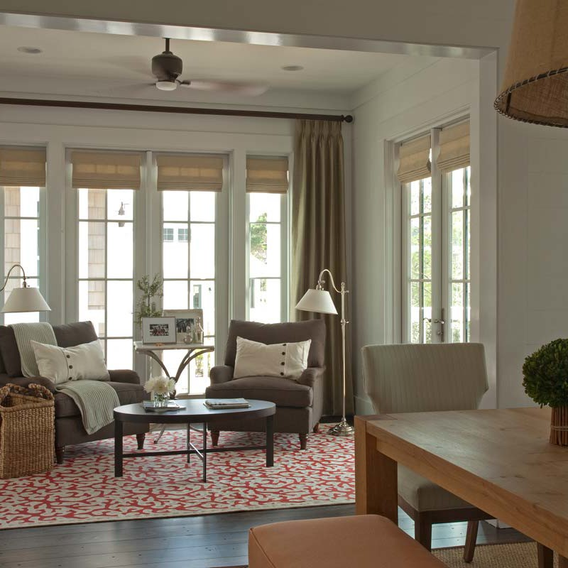 Living room with dark wood floors, white walls and comfortable furniture designed by Darci Hether New York