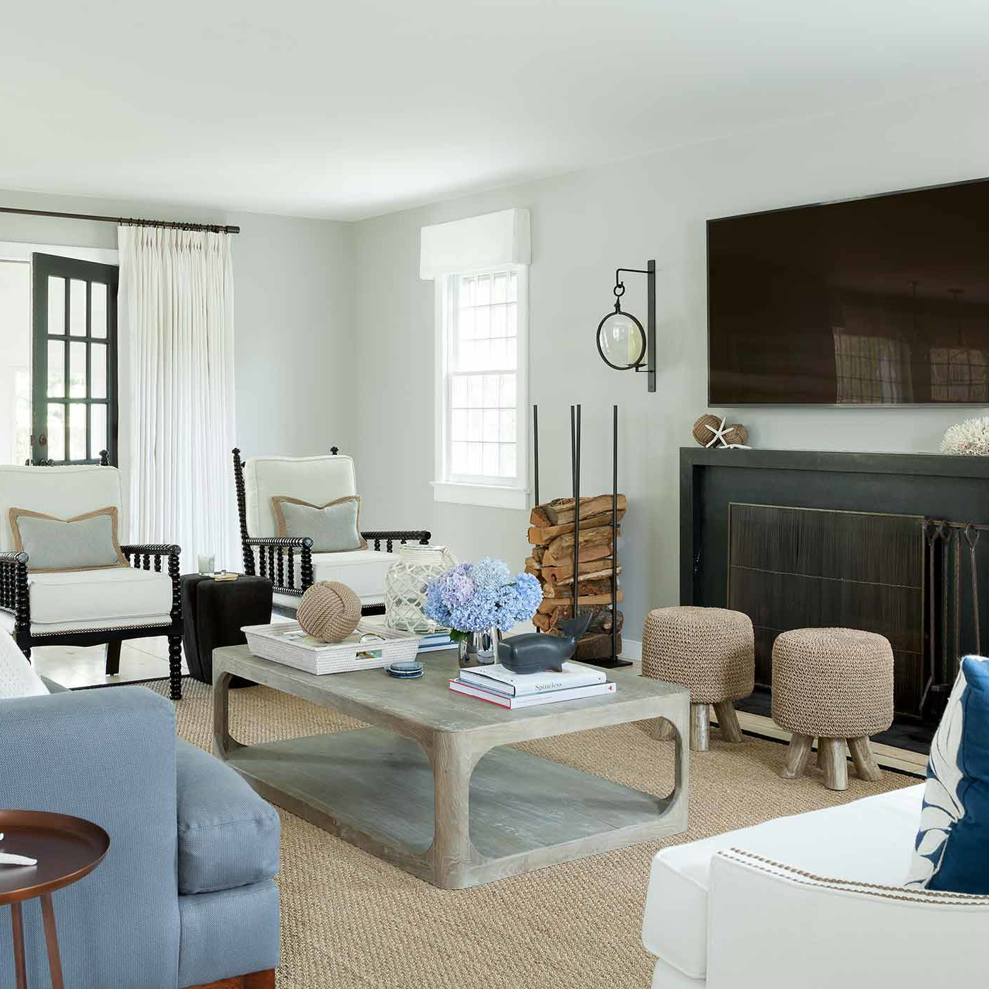 Living room with an array of sofas, chairs, and stools in Bridgehampton designed by Darci Hether New York