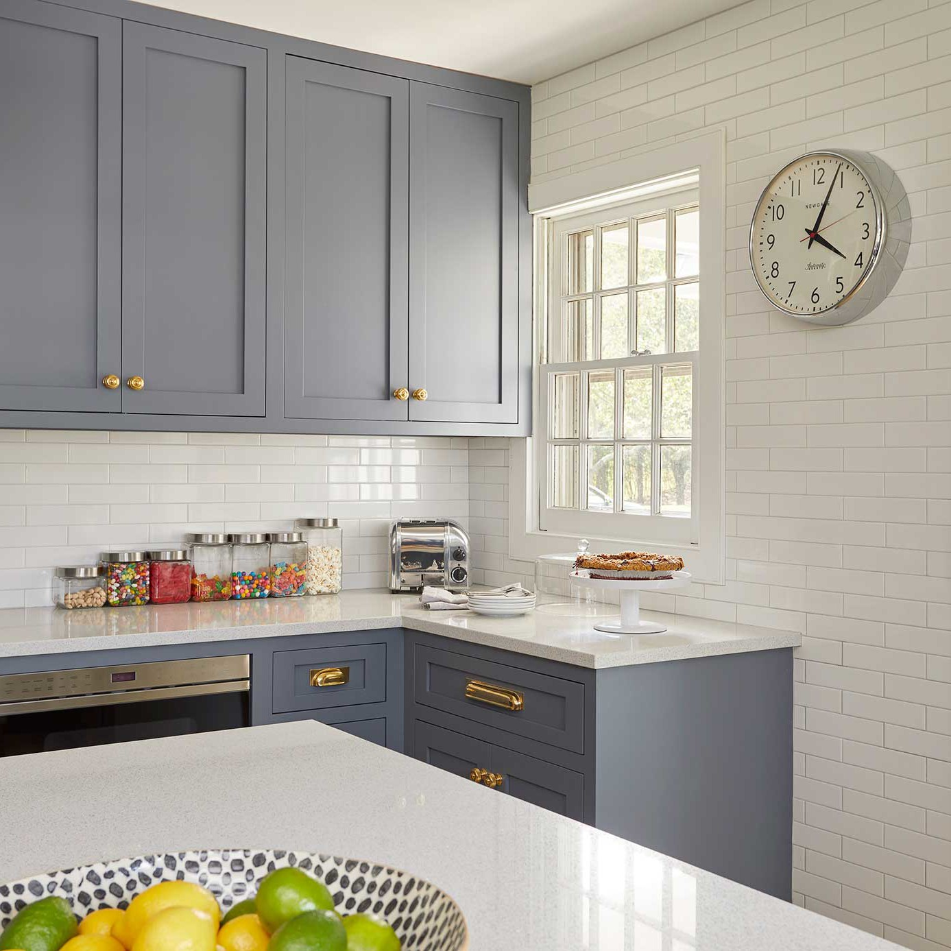 Bridgehampton kitchen with open shelving with brass mounts, perimeter cabinets, and a dark charcoal island