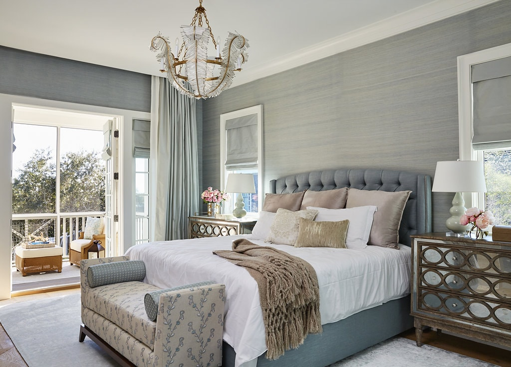 luxe florida beach house master bedroom with tufted bed, bench, mirrored dressers, and a chandelier. - darci hether new york