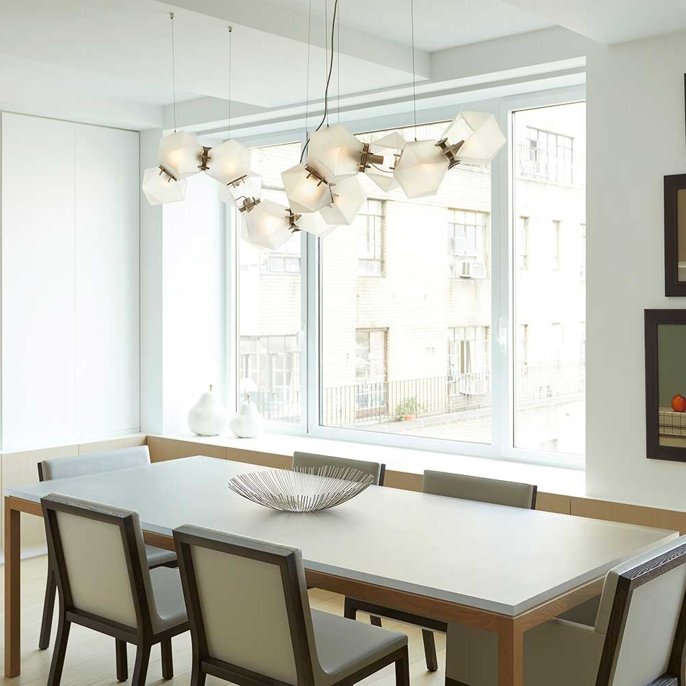 clean lined and contemporary dining room featuring a gabriel scott welles light fixture