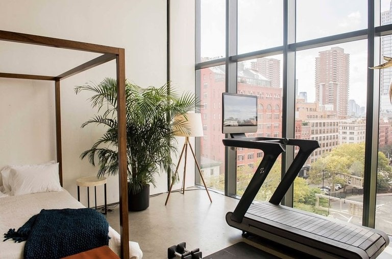a chic modern at home apartment gym featuring the peloton indoor bicycle. the at home gym overlooks a large metropolis city.