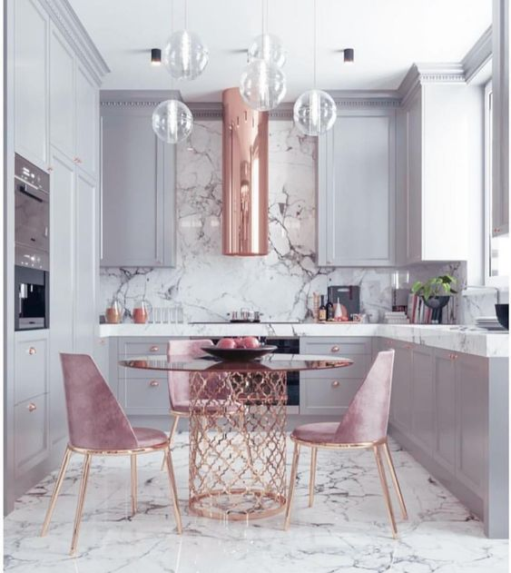 modern kitchen with marble counter tops and hanging glass lights. blush upholstered chairs are seated around a circular bronze table.