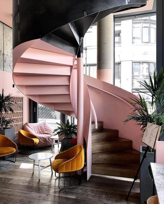 pink and black spiraal staircase in hotel lobby with hardwood floors