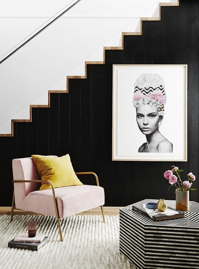 a modern living room with black painted stairs and white and black striped hexagon table. Beside the table is a modern blush chair with a gold frame.