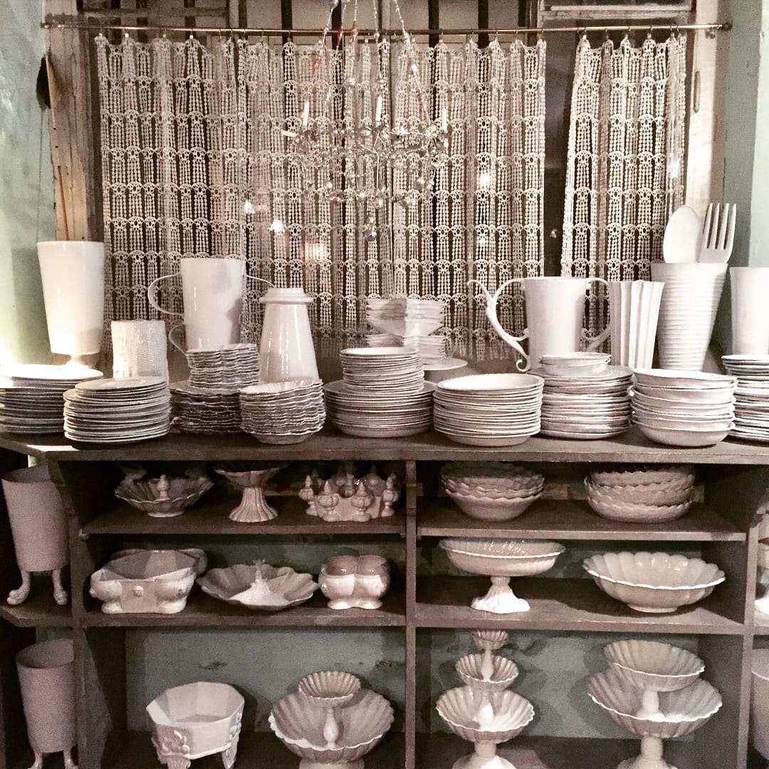 shelves of white dishes from darci hether's receent trip to astier de villatte in paris