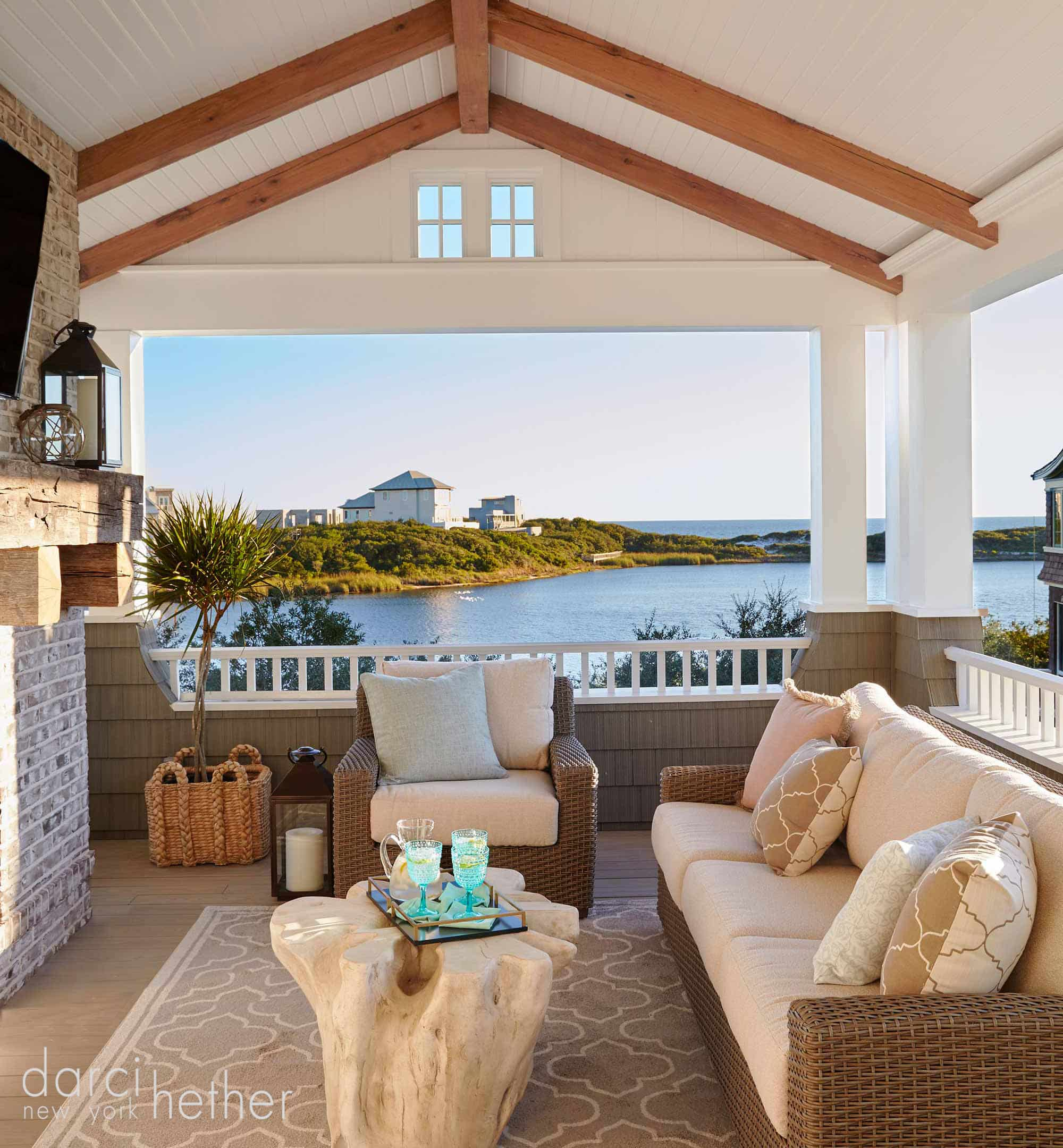 outdoor living room with tv above fireplace of new beach house build in watersound florida 30A. design by darci hether new york.