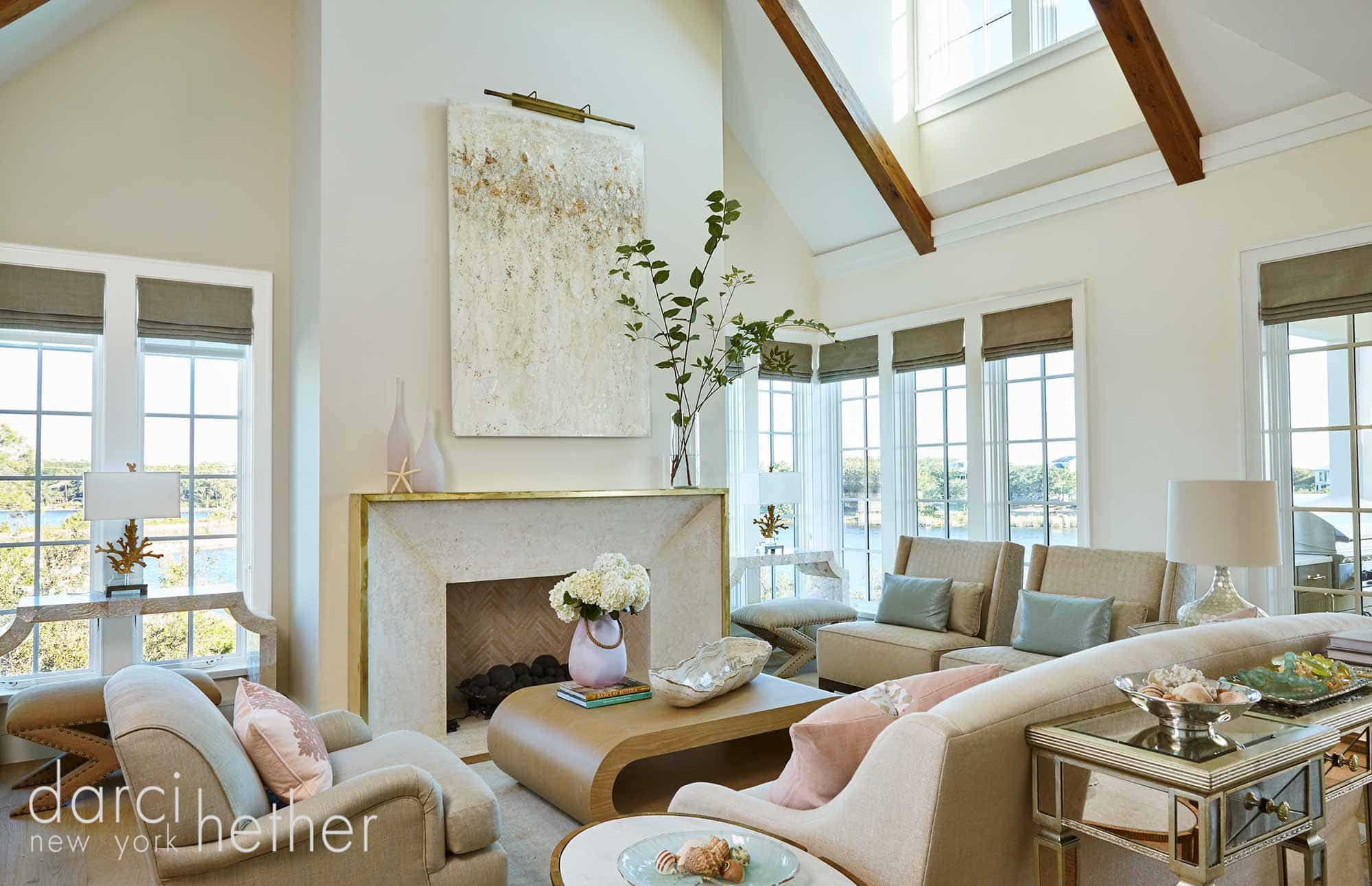great room with beach tones and a gold metal fireplace surround and blush accents of watersound florida beach house designed by darci hether new york.