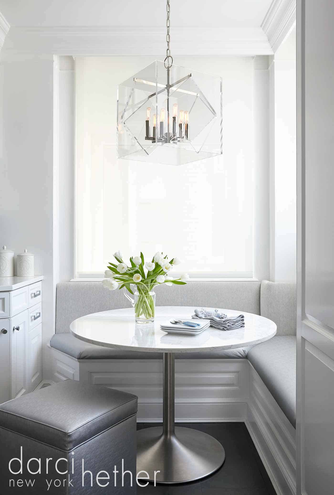 chic 5th avenue apartment with views of central park. the acrylic pendant lighting and silver metallic accents create an elevated dining experience.