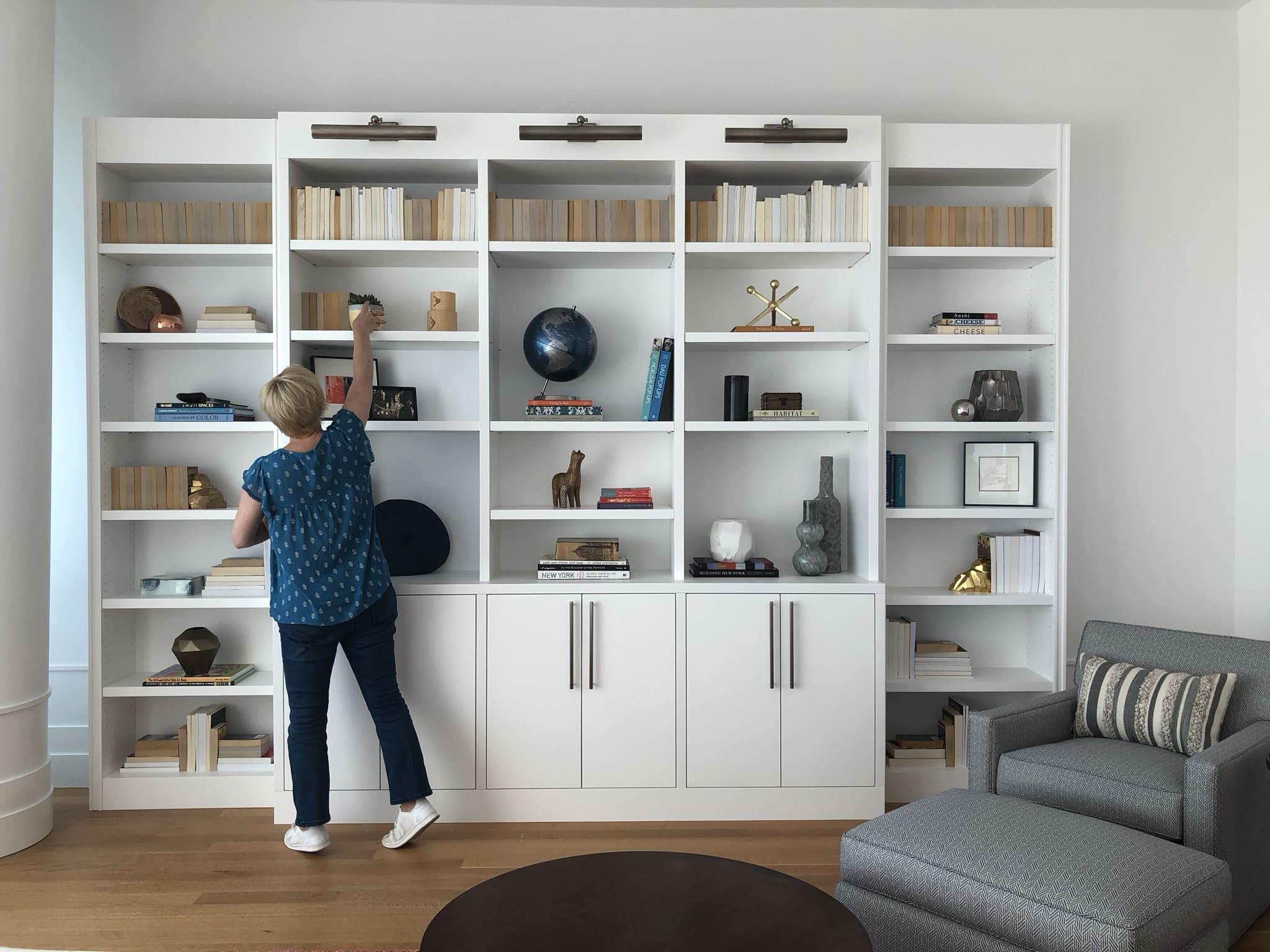 final stages of bookcase styling tutorial given by designer darci hether. session takes place in a midtown apartment in new york city.