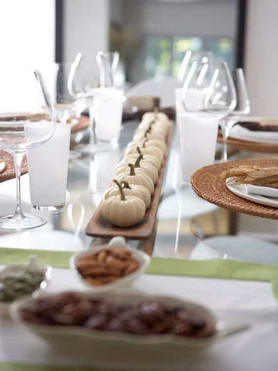 thanksgiving tablescape with white pumpkins and clear glassware and wicker chargers.