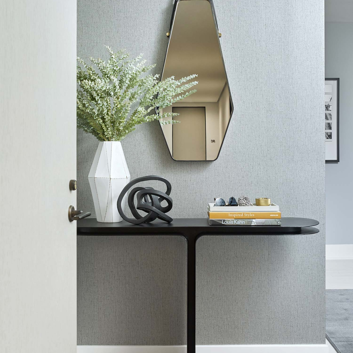 Entryway with dark gray, deeply textured wallpaper, angular mirror and black metal table in a NYC home