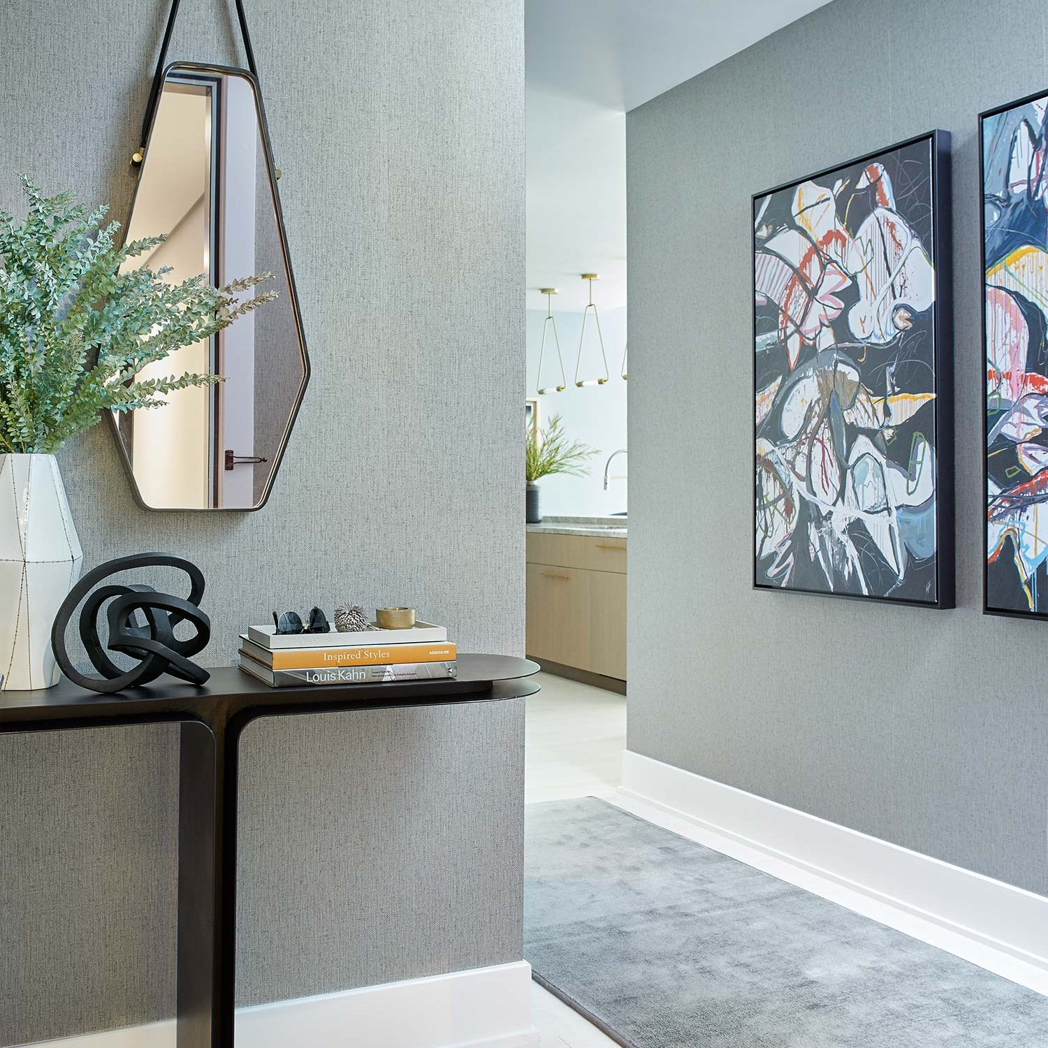 Entryway design with dark gray, deeply textured wallpaper, angular mirror, black metal table and oversized artworks