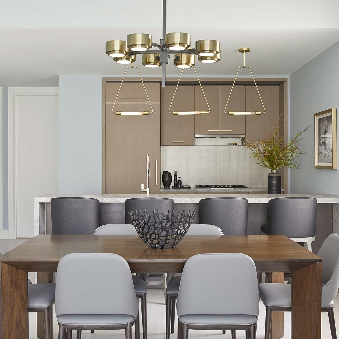Open kitchen and dining with statement metal lights and art in a brass frame in a NYC interior design project