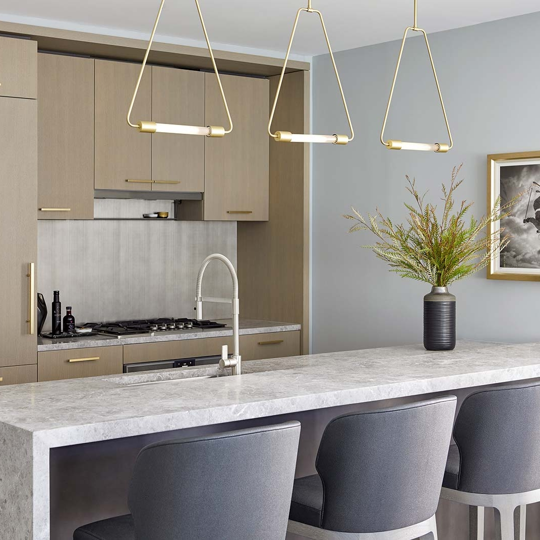 Open kitchen design with wood cabinets, waterfall stone countertop, sleek cabinets and statement metal lights