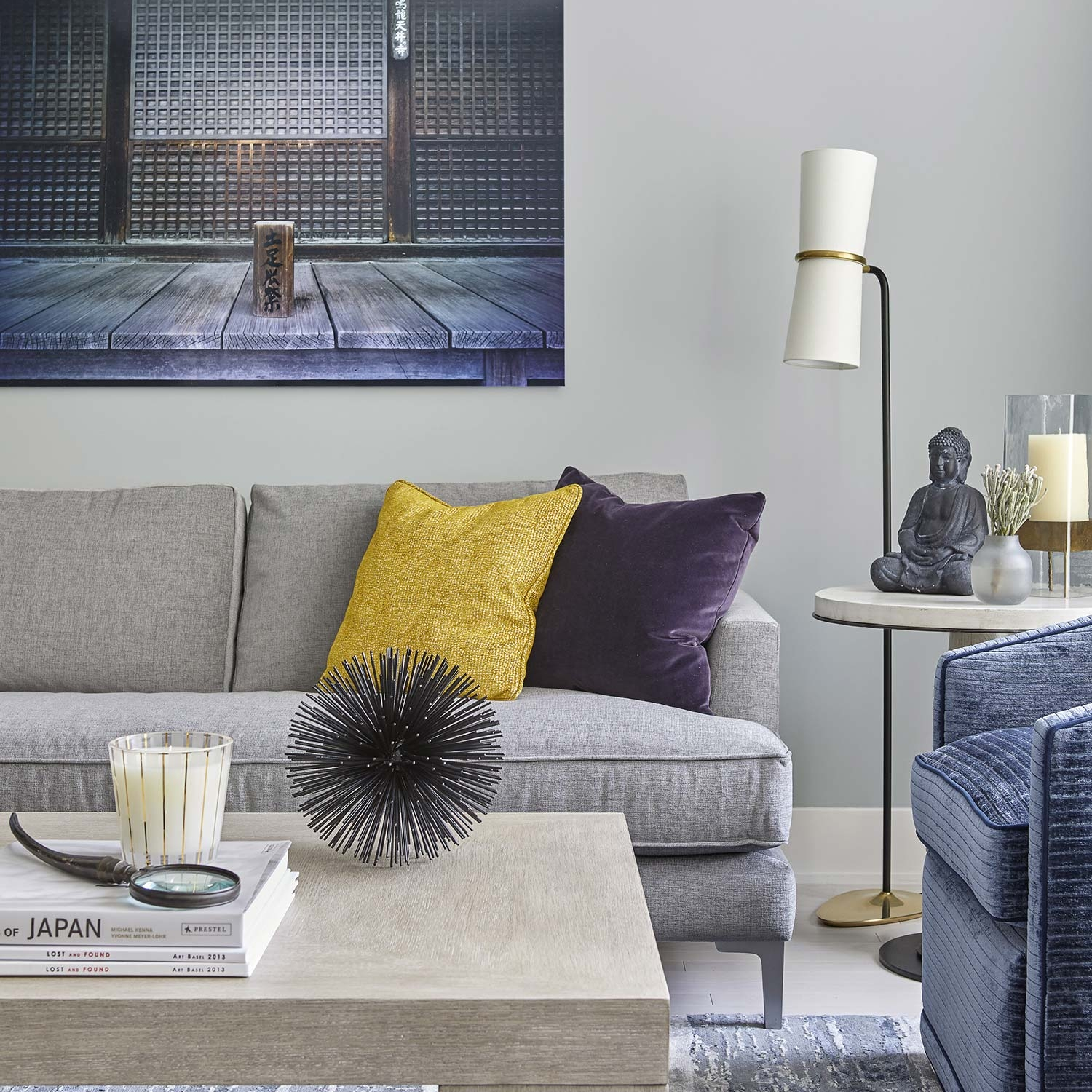 NYC apartment living room featuring textured contemporary furniture, throw pillows, japanese art and the stone buddha