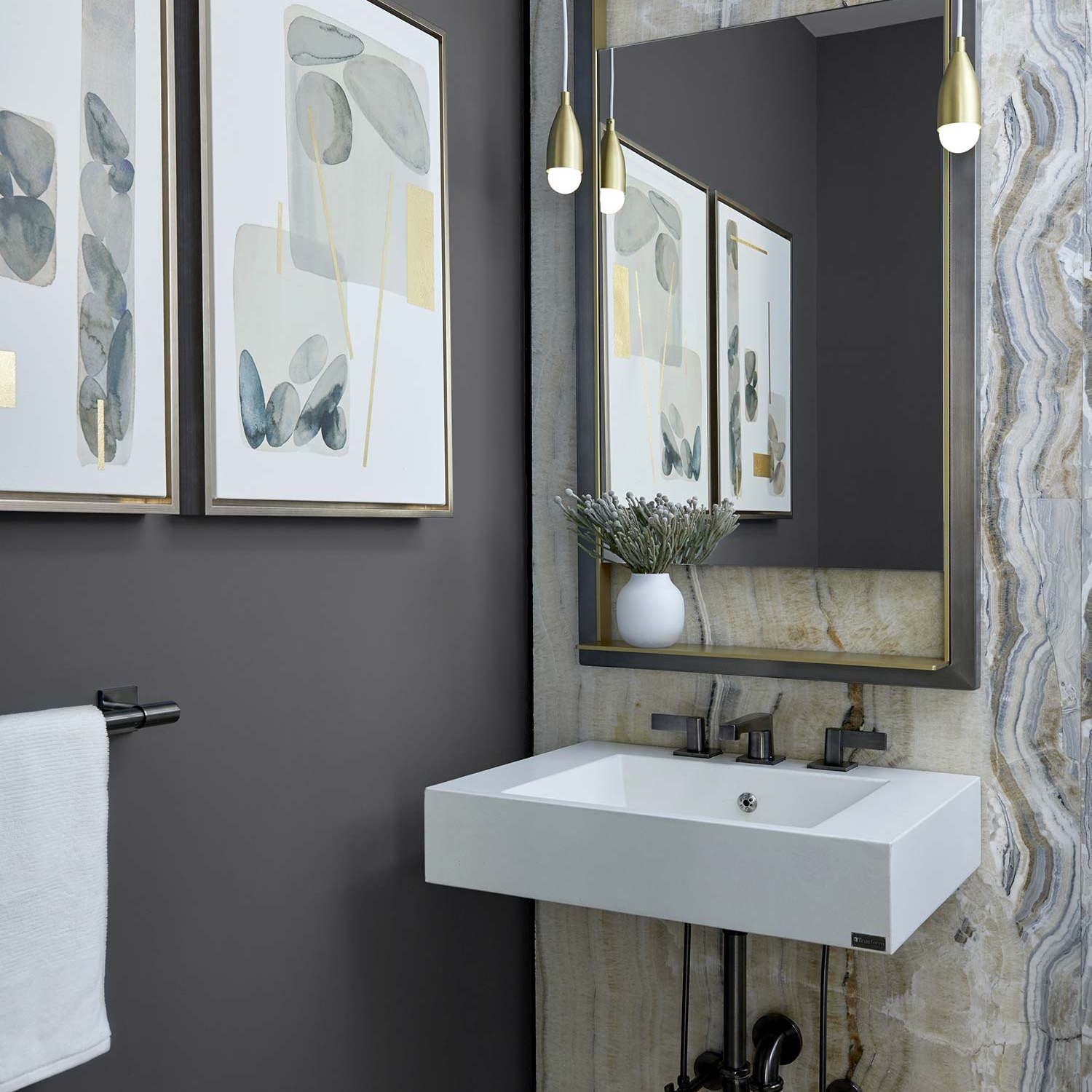 Powder room design with modern brass pendants, warm-toned natural stone, deep-toned walls, and organic-inspired artwork