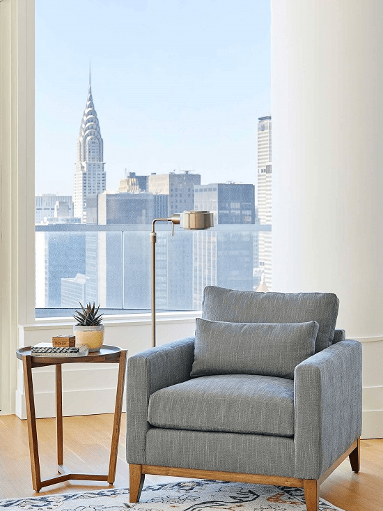 darci-hether-new-york_interior-designer_the-3-apartment-types-in-nyc_what-you-need-to-know_moder-new-build-apartment-reading-chair-with-city-views