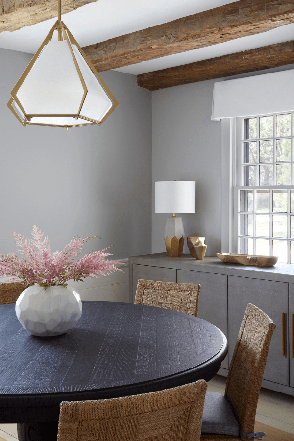 gabriel scott light fixture dining room exposed beams textured wood chairs hamptons home darci hether ny