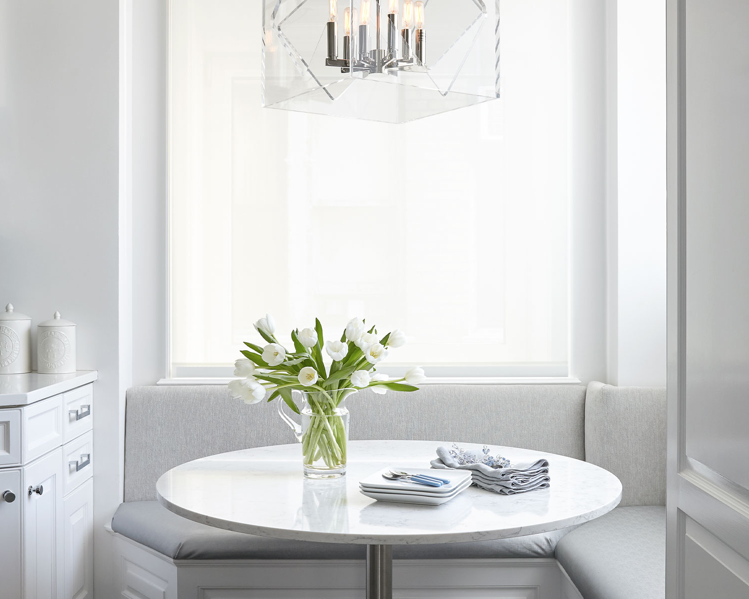 Eat-in breakfast nook, upholstered banquette seat and cube ottoman seating in a NYC interior design project