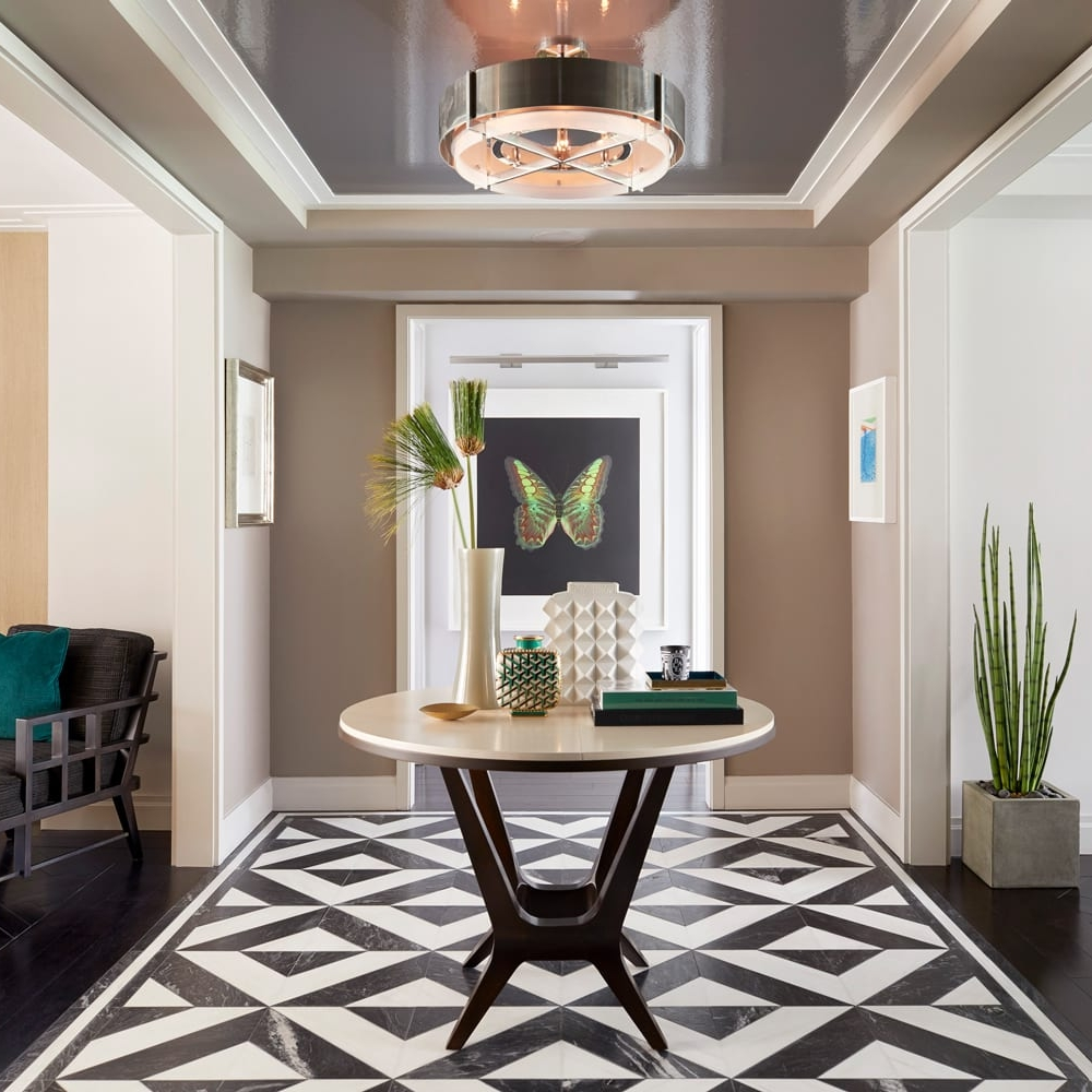 Entryway with high-gloss wallpaper on the ceiling, a light fixture, black and white marble floor and a svelte table in NYC